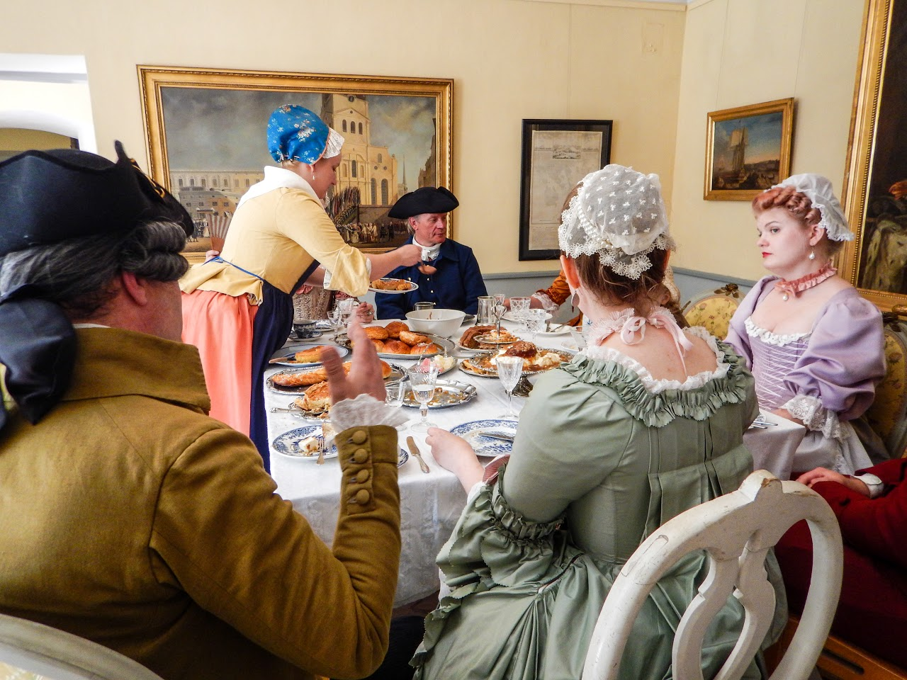Women sitting at a table in 18th century style clothes.